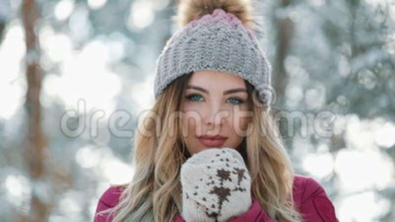 95f357fe7bc Pretty Woman In Winter Hat Smiles Standing Outside On The Snow In The  Forest. Portrait Of A Beautiful Girl Looking Into Stock Video - Video of  festive