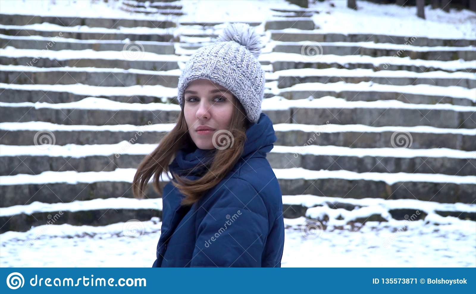 7cd56decd14 Pretty woman in winter hat smiles standing outside on the snow in the  forest with snowy