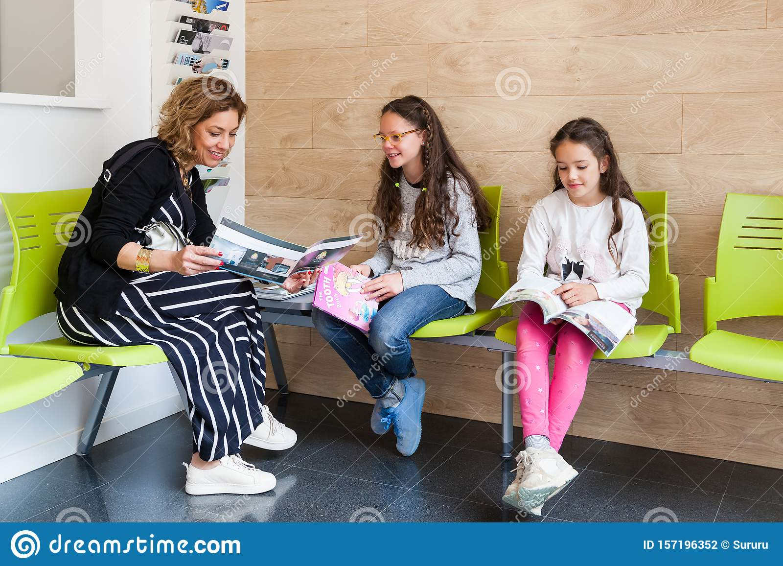 Two Young Girls With Their Mother Sitting In The Waiting Room Of A Medical Clinic Stock Photo Image Of Hospital Decor 157196352