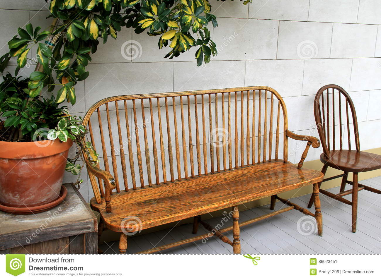 Download Pretty Wood Benches And Chairs With Large Potted Plants On Table  Nearby Stock Image