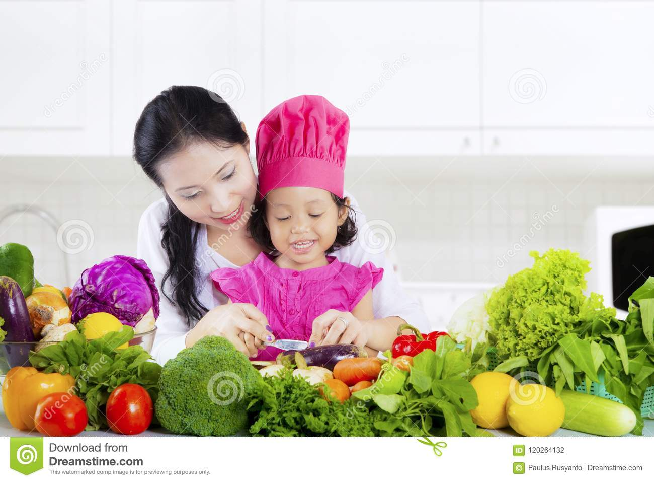Pretty woman and daughter cut vegetables