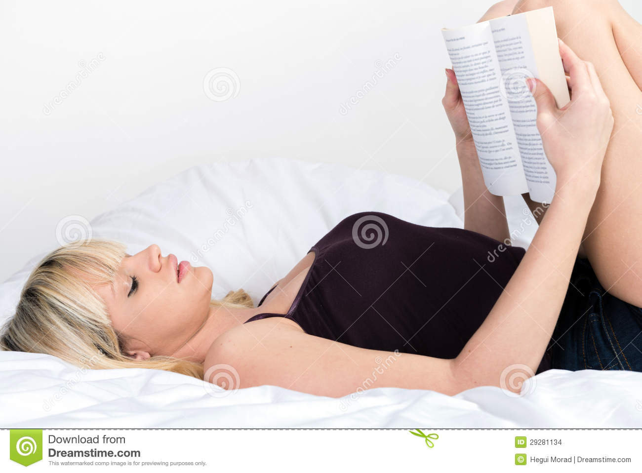 Pretty Young Blond Girl Reading Book Lying In Her Bed