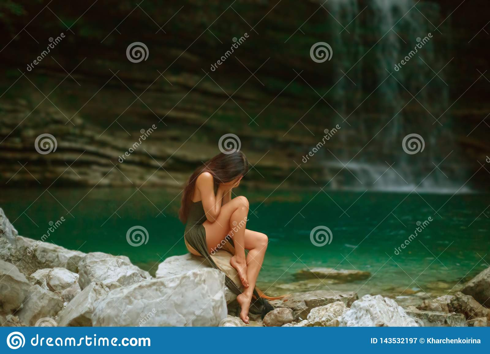 Pretty young crying girl with dark black long hair sitting alone in lagoon of Martvili Canyon, lady in long green cut