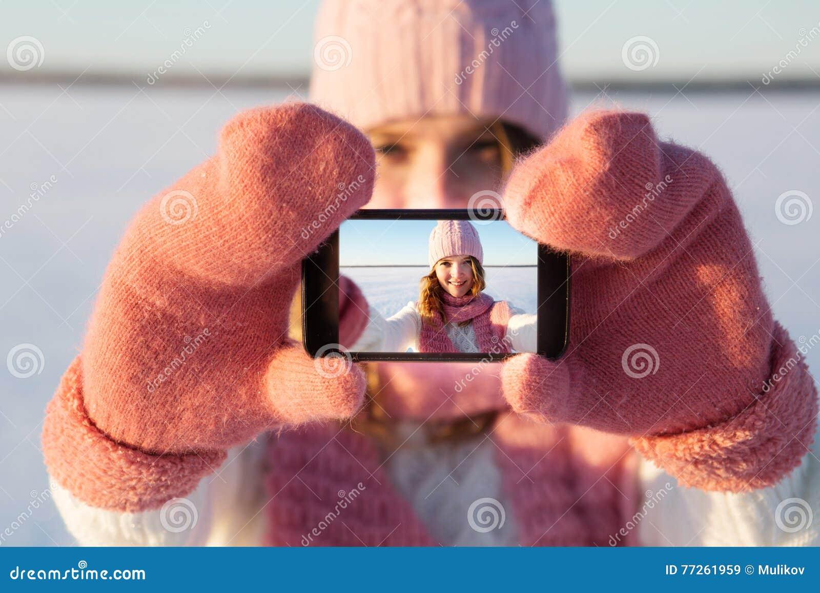 Pretty young female tourist takes selfie in winter