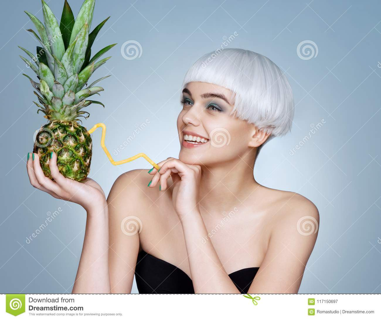 Pretty young girl with pineapple cocktail.