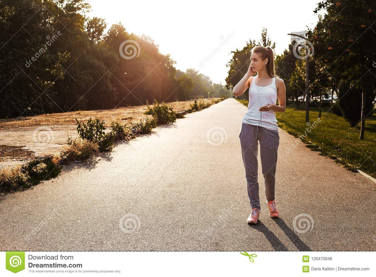 The pretty young girl in sport clothes walking on the road and listen music on her smartphone