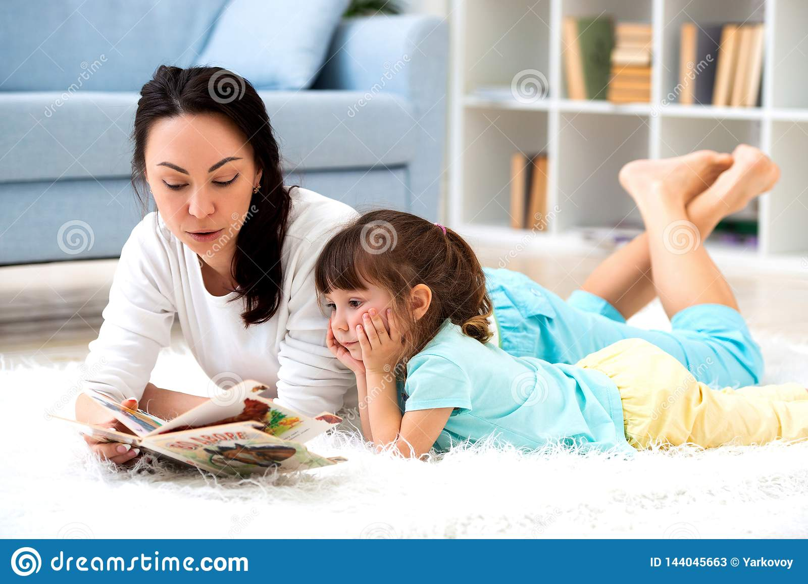 Pretty young mother reading book her little daughter, lying on the carpet on the floor in home