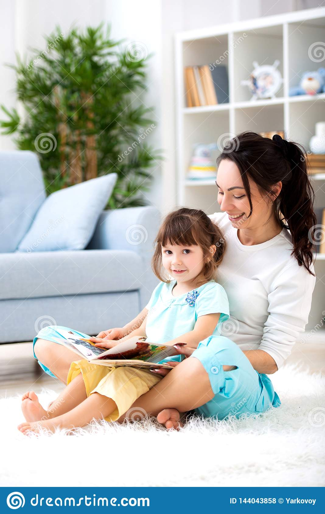 Pretty young mother reading a book to her daughter sitting on the carpet on the floor in the room. Reading with children