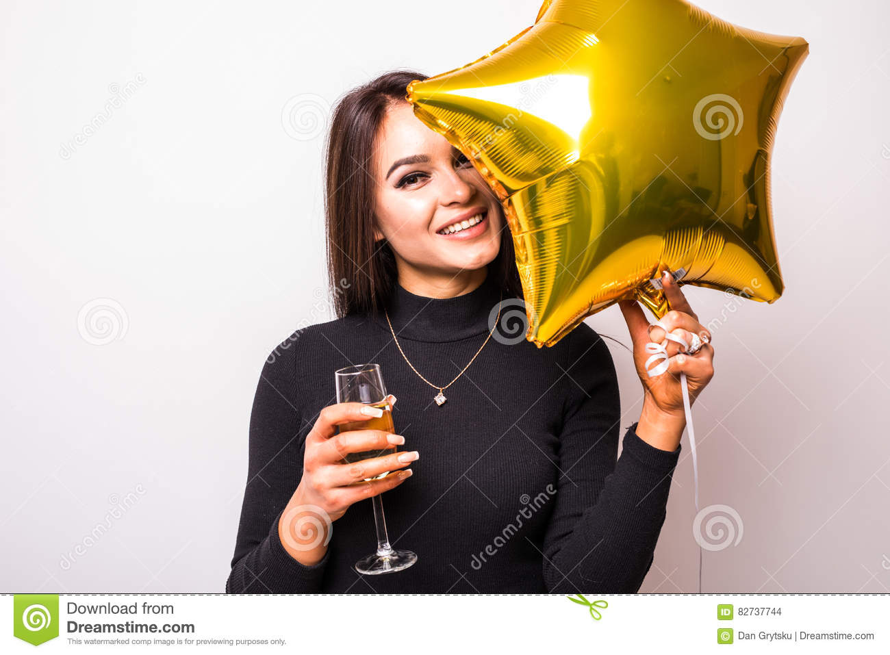 59480f93ecdd Pretty young woman in black dress with gold star shaped balloon smiling and drinking  champagne over white background