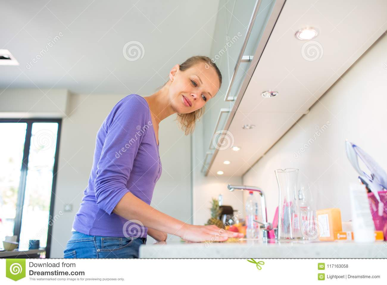 Pretty, Young Woman Cleaning Her Modern Kitchen Stock ...