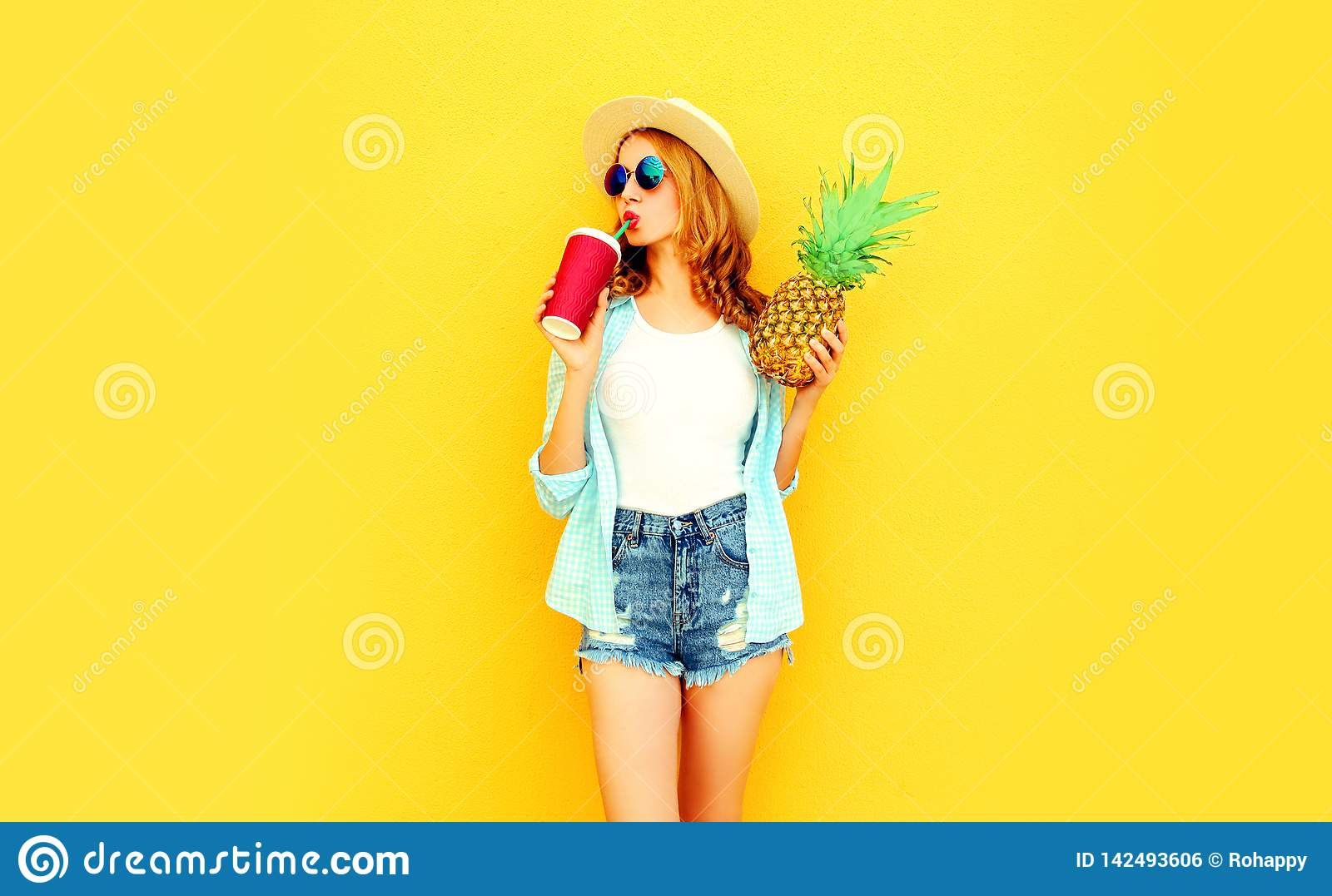 pretty young woman drinking juice, holding pineapple in summer straw hat, sunglasses, shorts on colorful yellow