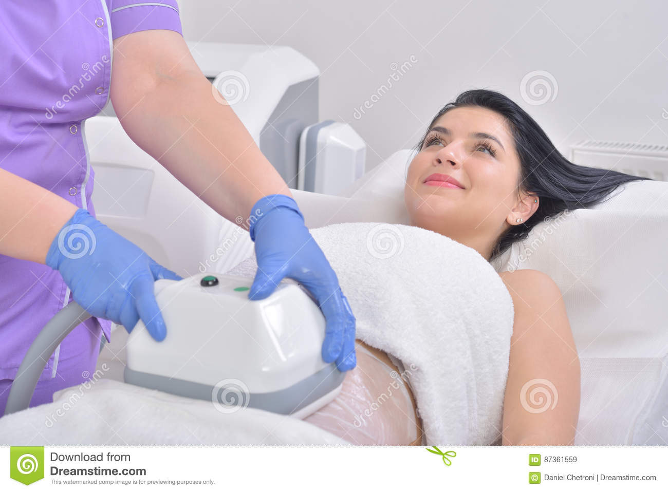 Pretty young woman getting cryolipolyse fat treatment in profess