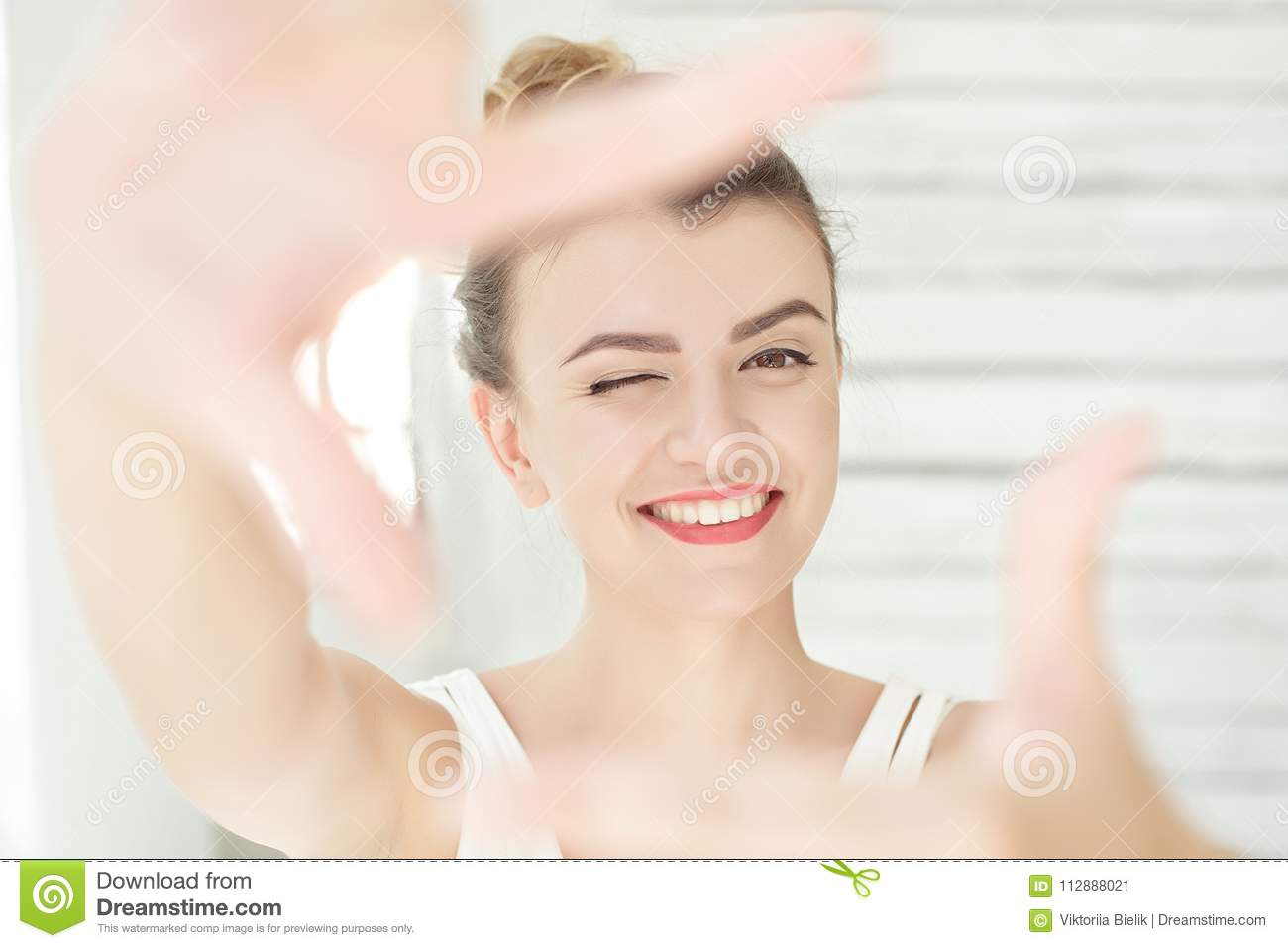 Pretty young woman making a frame gesture