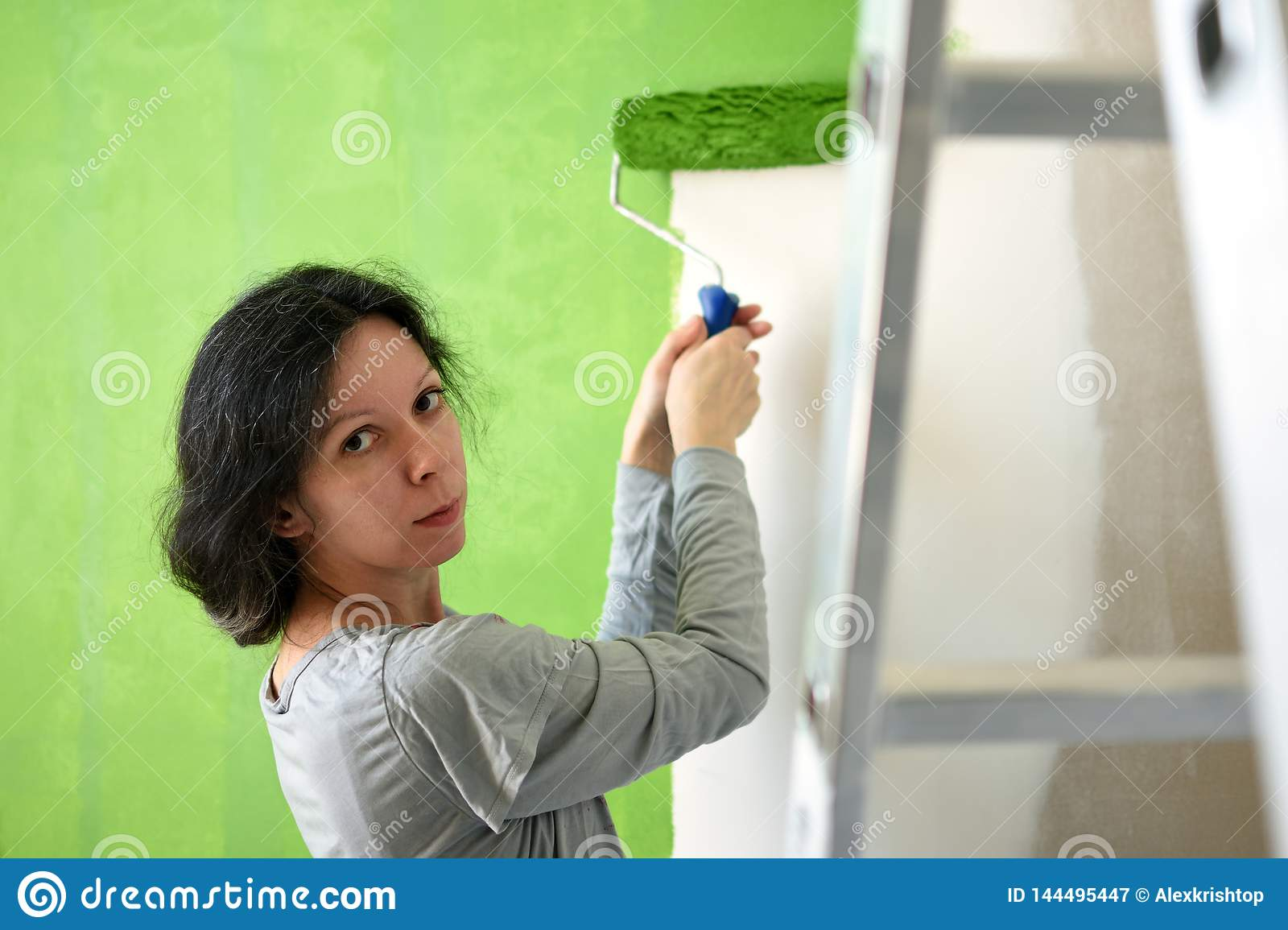 Pretty young woman painting green interior wall with roller in a new home