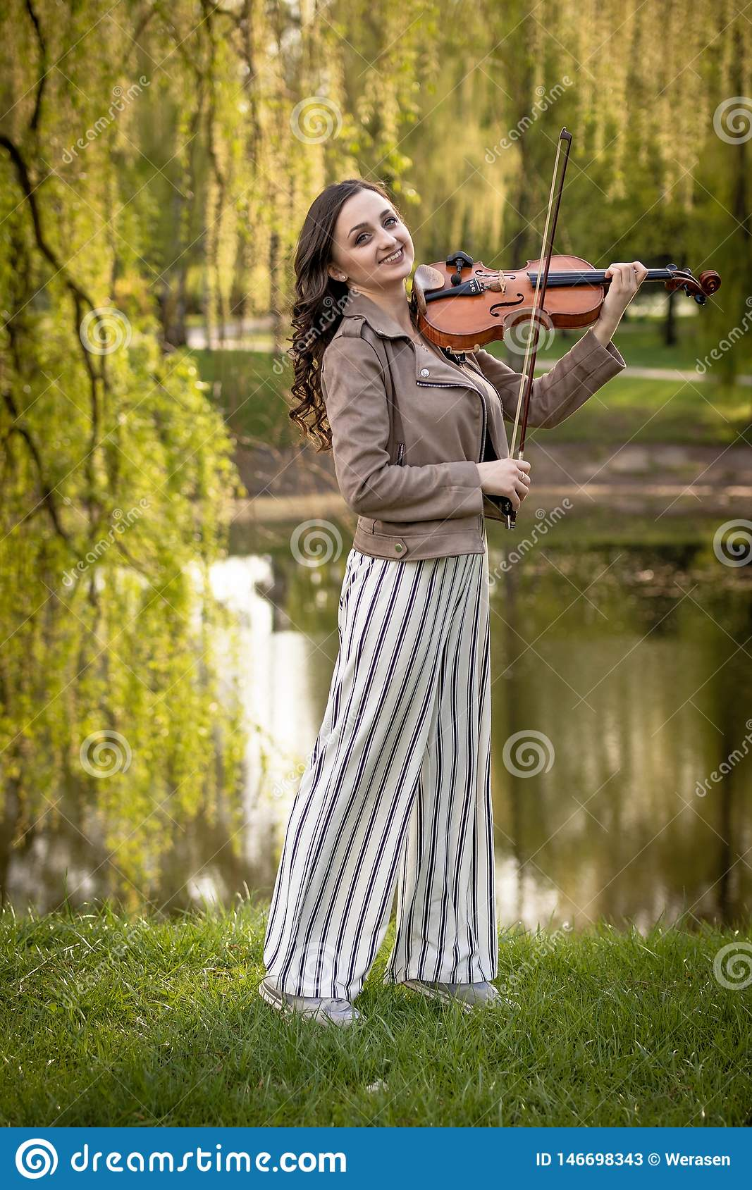 Pretty young woman playing the violin in the park and smiles, Full-length portrait