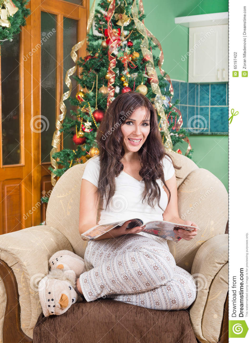 d5c8daf5466e9b Pretty Young Woman Reading Magazine Sitting on Sofa Smiling Wearing Pajamas  and Fluffy Slippers with Christmas Tree Behind , Home and Leisure Concept