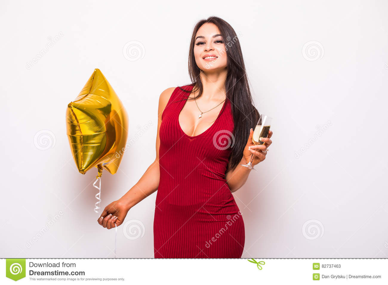 7dd0b44b3685 Pretty young woman in red dress with gold star shaped balloon smiling and drinking  champagne over white background