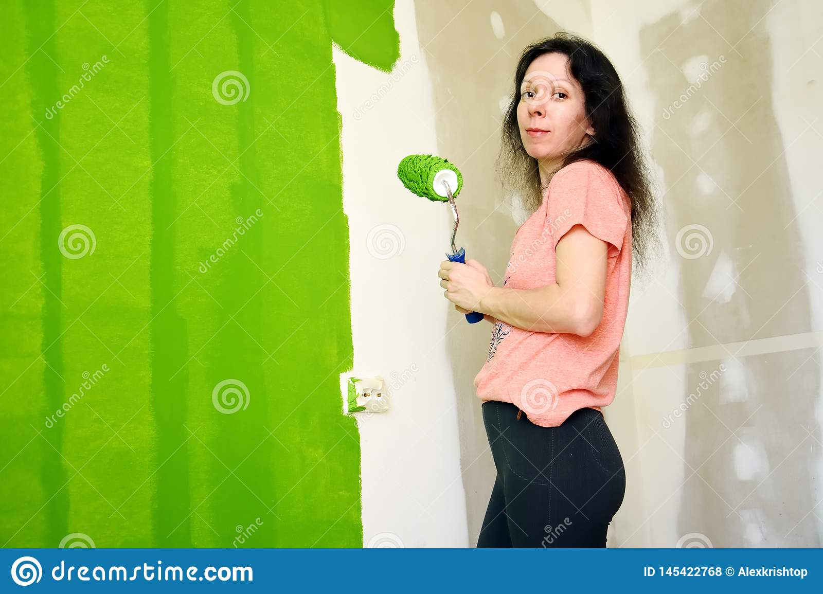 Pretty young woman in pink t-shirt is smiling and keeping roller, painting green interior wall in a new home