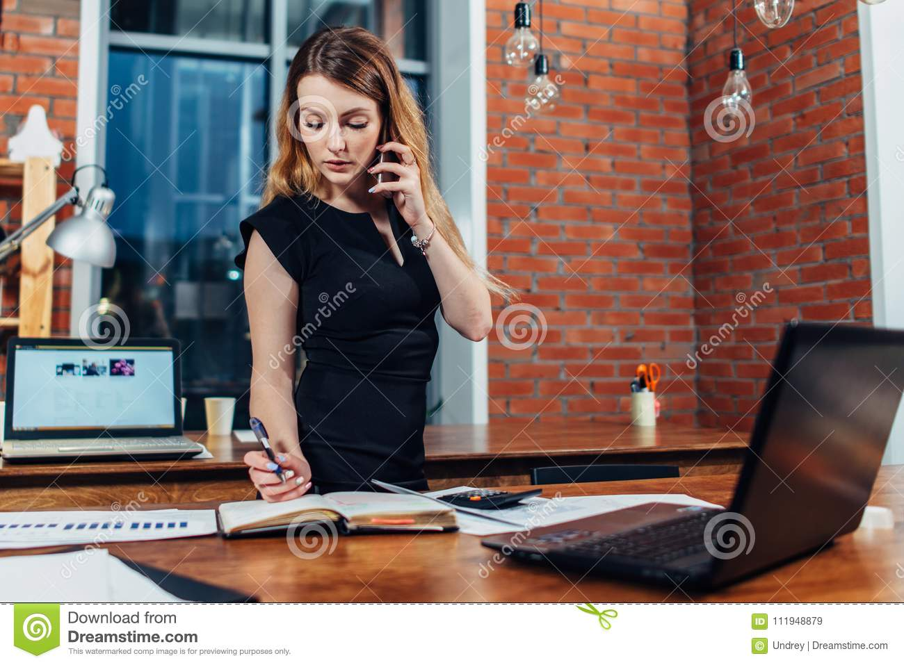 Pretty young woman talking on phone counting using a calculator working at office standing at desk
