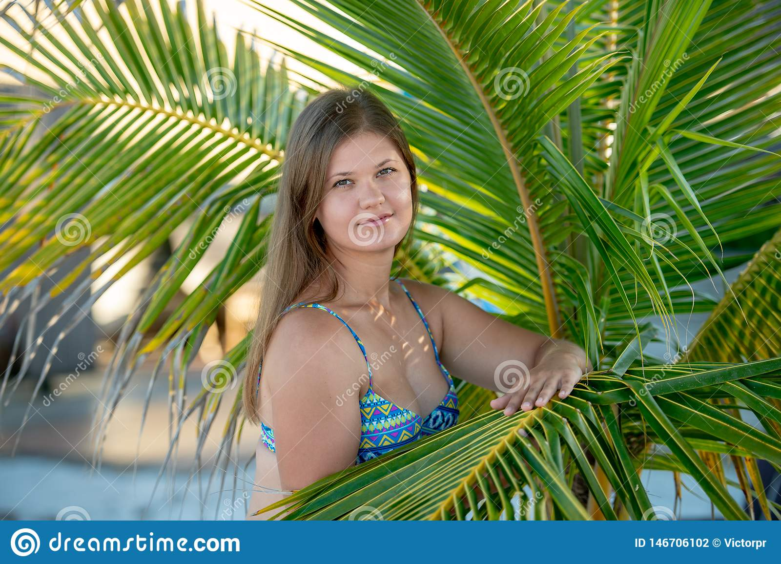 Pretty young woman under the palm tree
