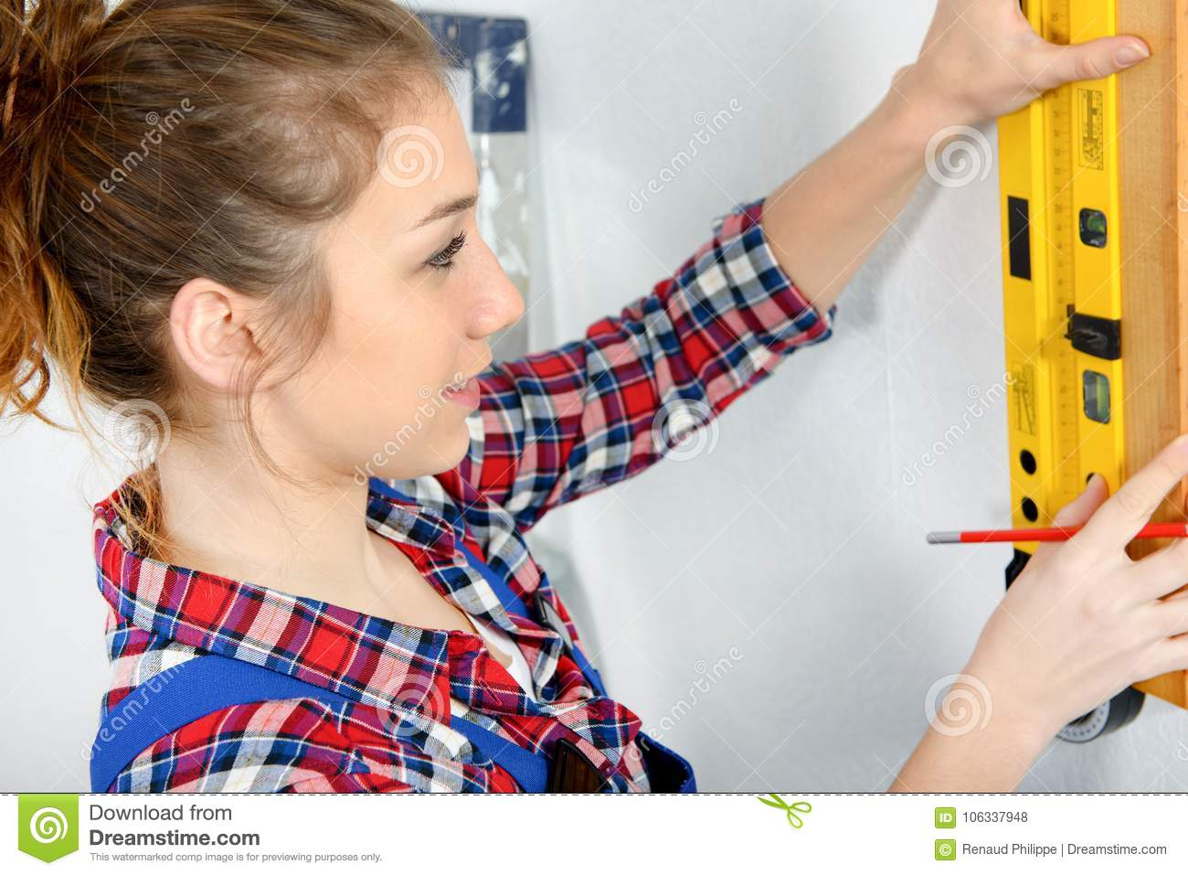 Pretty young woman using spirit level