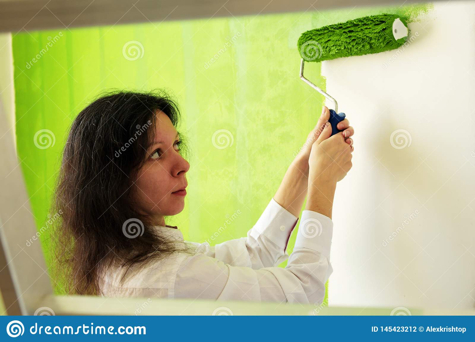 Pretty young woman in a white shirt is carefully painting green interior wall with roller in a new home
