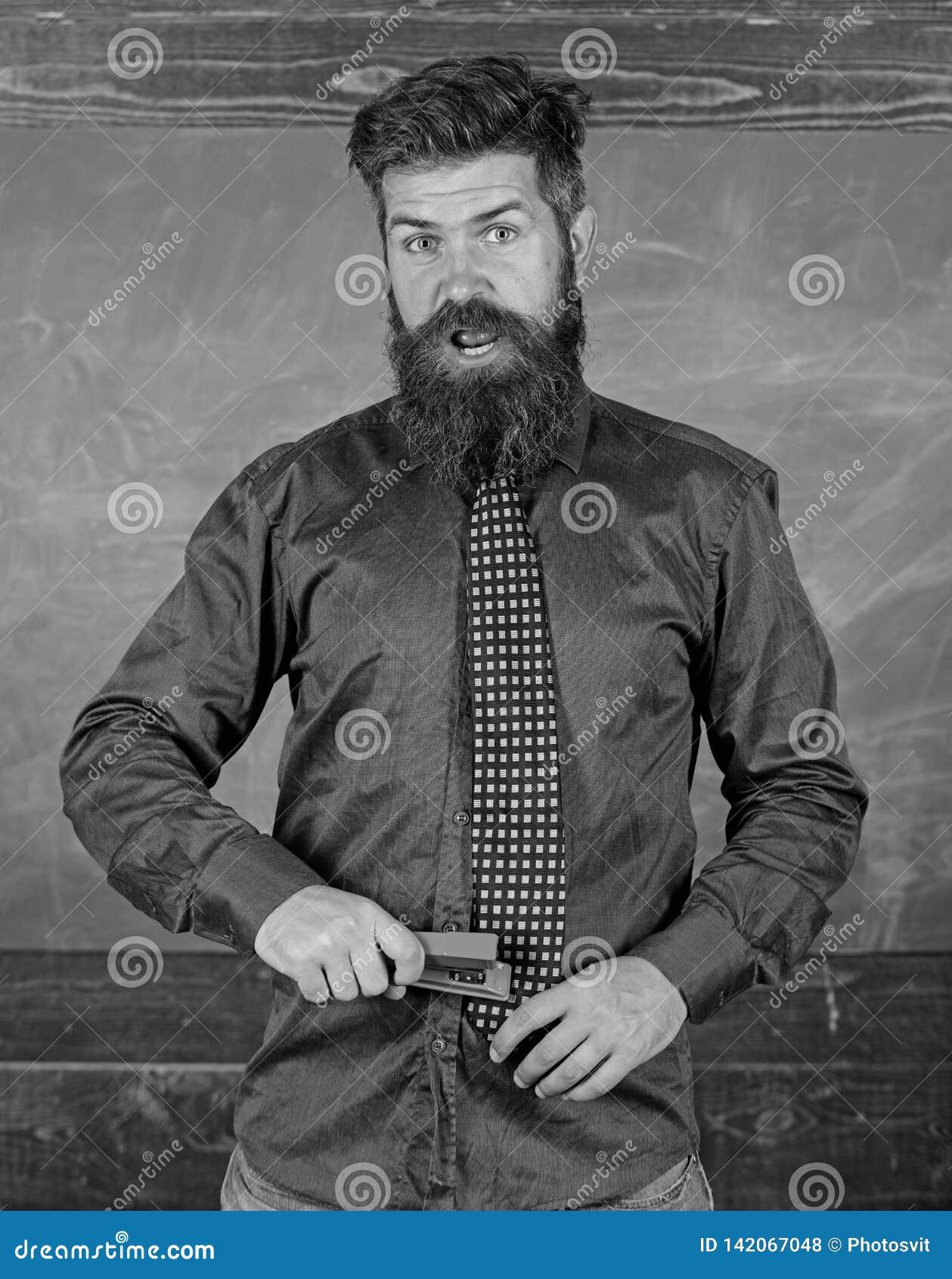 Prevención de accidentes de la escuela Hombre barbudo del profesor con el fondo rosado de la pizarra de la grapadora Enseñe el pa