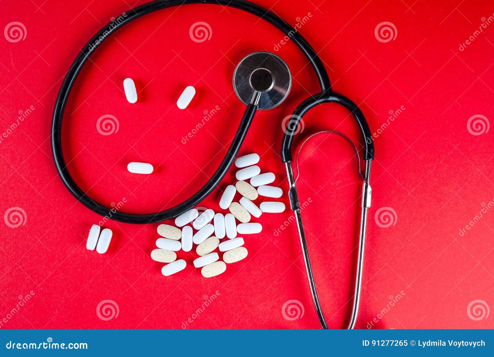 Preventivpillerar, minnestavlor och stetoskop på vit bakgrund