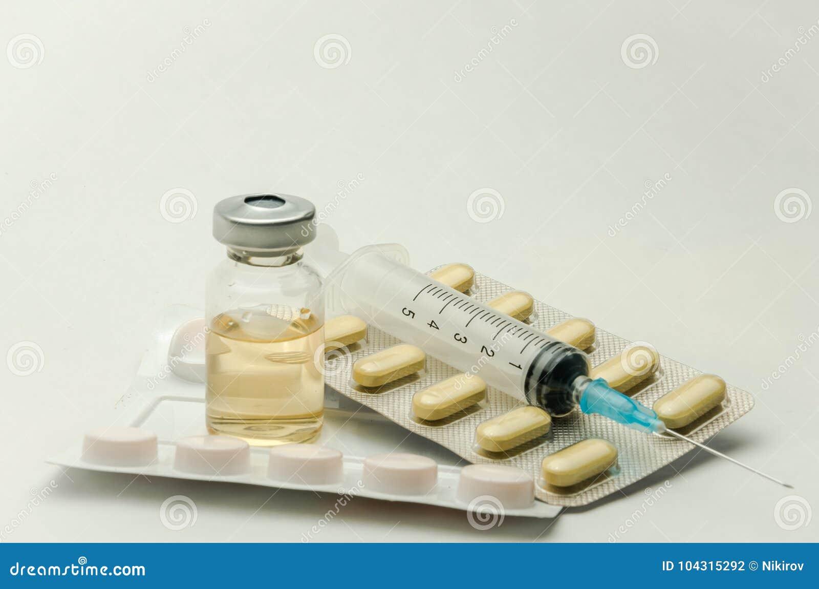 Preventivpillerar, vitaminer och injektionsspruta för injektion med läkarbehandlingar som isoleras på vit bakgrund