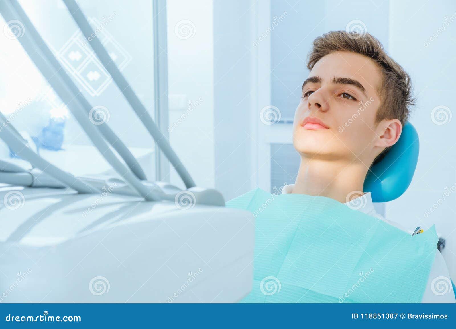 Prevenzione della carie dentale Adolescente alla sedia del ` s del dentista durante la procedura dentaria, alto vicino di sorriso