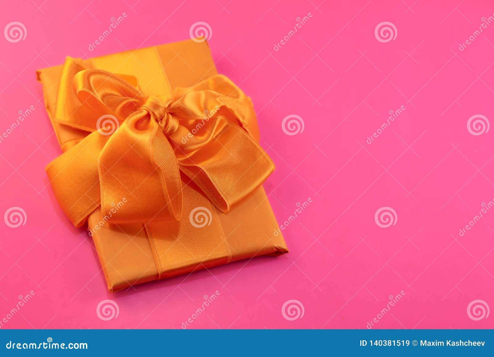Prezent pakuje i dekoruje z żółtym łękiem na różowym tle z kopii przestrzenią Mieszkanie nieatutowy, odgórny widok kosmos kopii