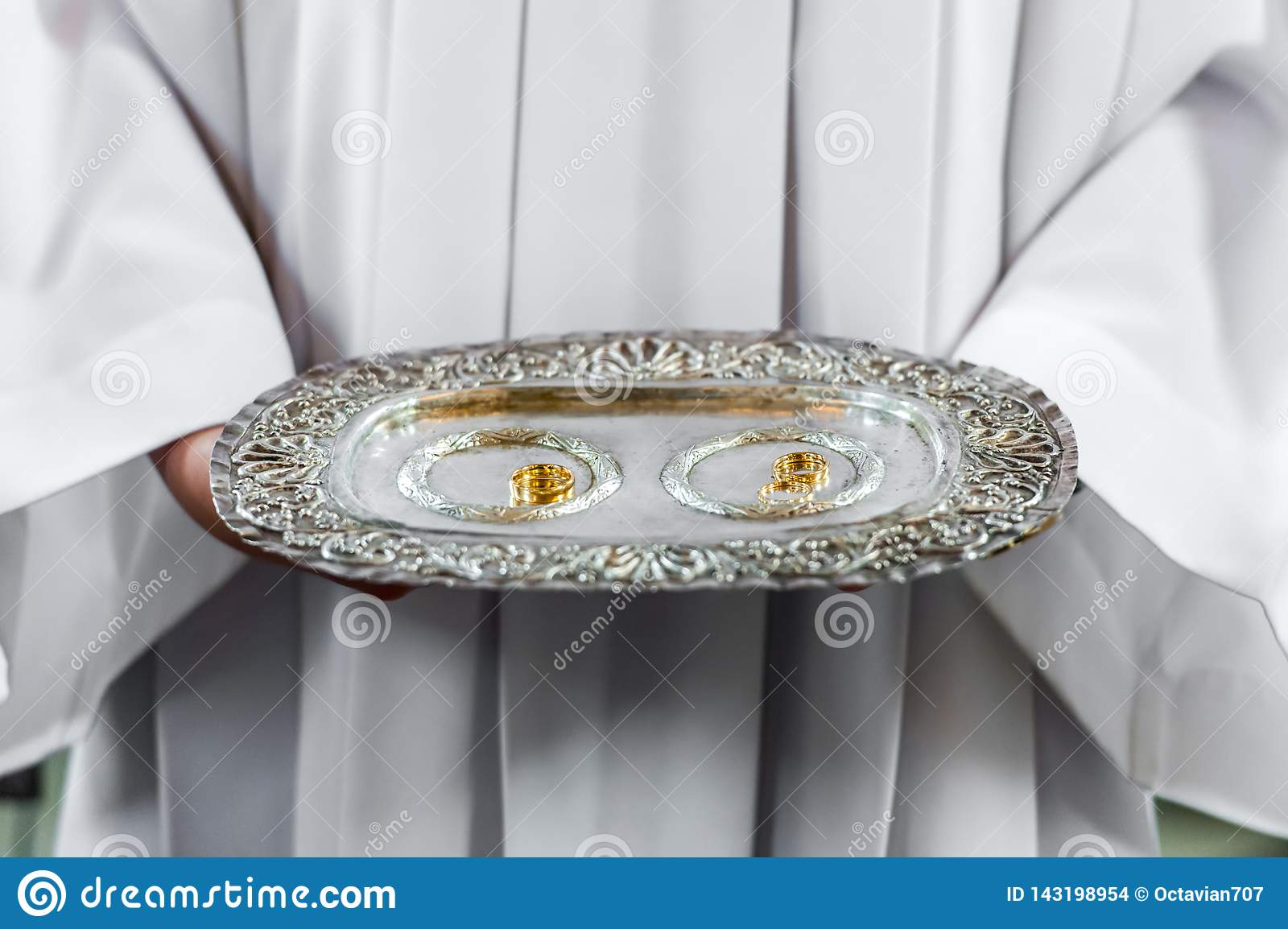 Priest and wedding rings on silver platter