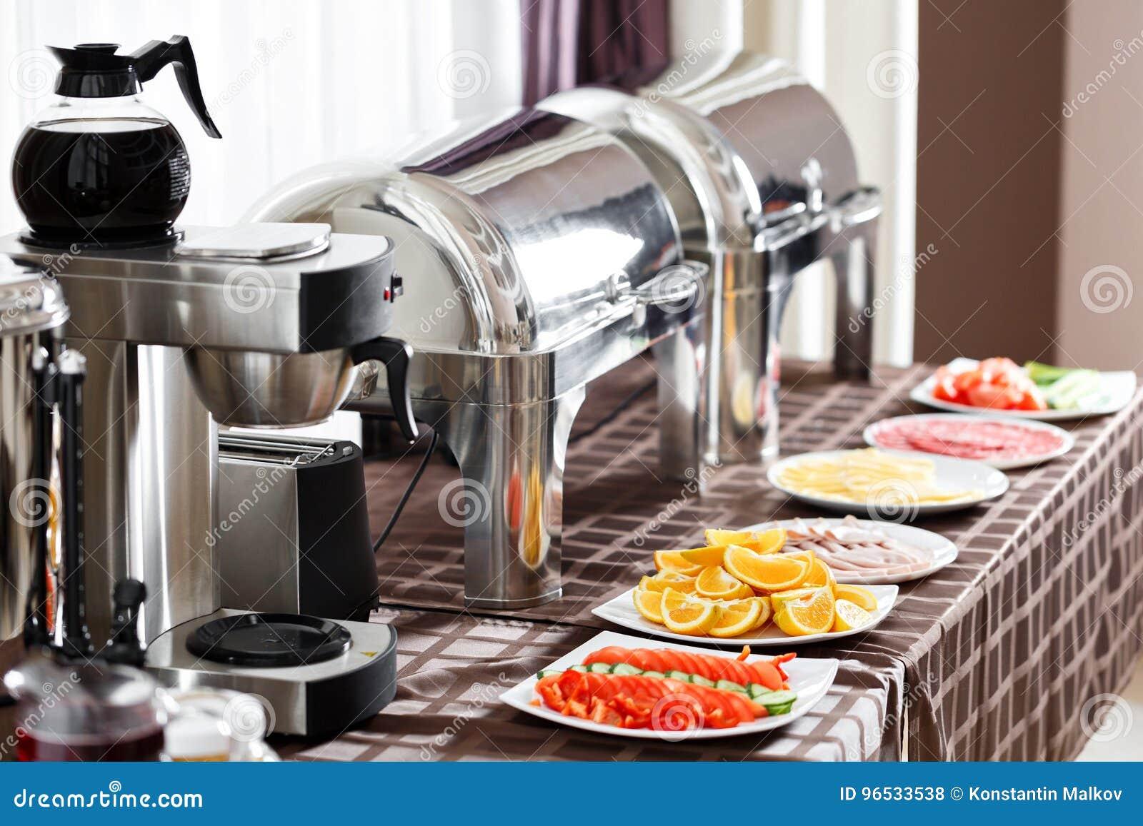 Prima colazione all hotel Tavola di buffet con gli ospiti aspettanti delle stoviglie