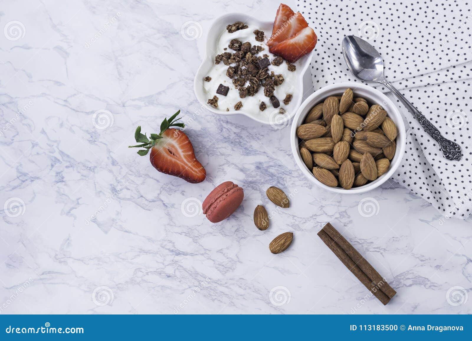Prima colazione alla moda decorata e sana - fragole, yogurt con granola e mandorle su un fondo di marmo bianco