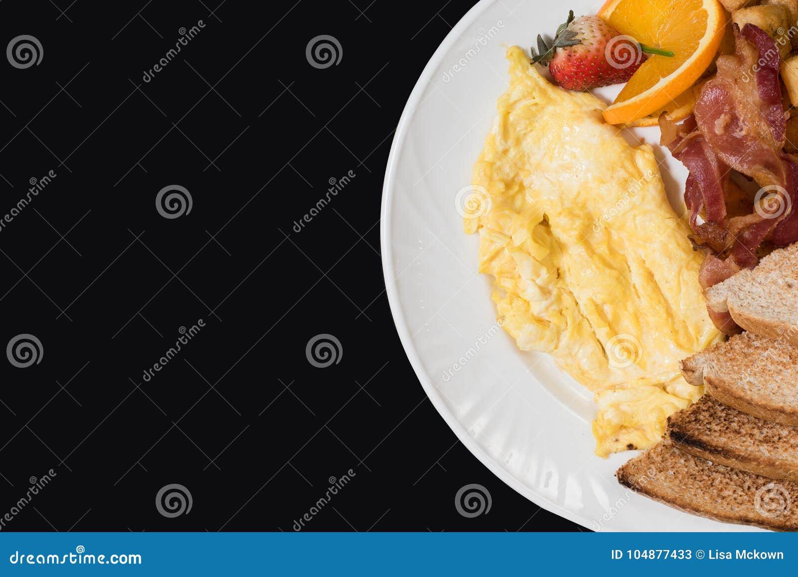 Prima colazione con bacon, le uova ed il pane tostato