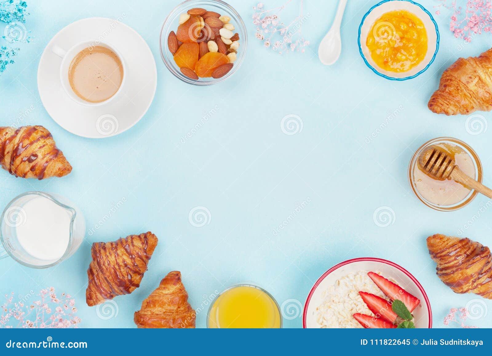 Prima colazione continentale di mattina con caffè, il croissant, la farina d avena, l inceppamento, il miele ed il succo sulla vi