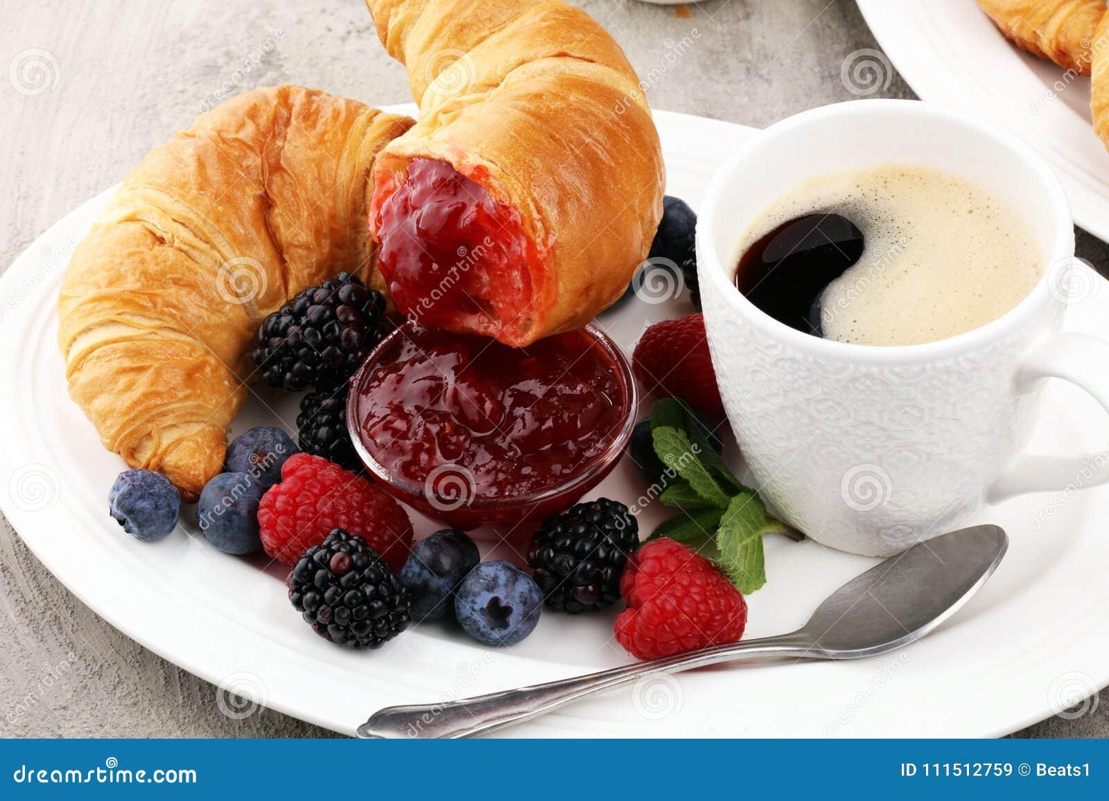 Prima colazione deliziosa con i croissant freschi e bacche mature e J