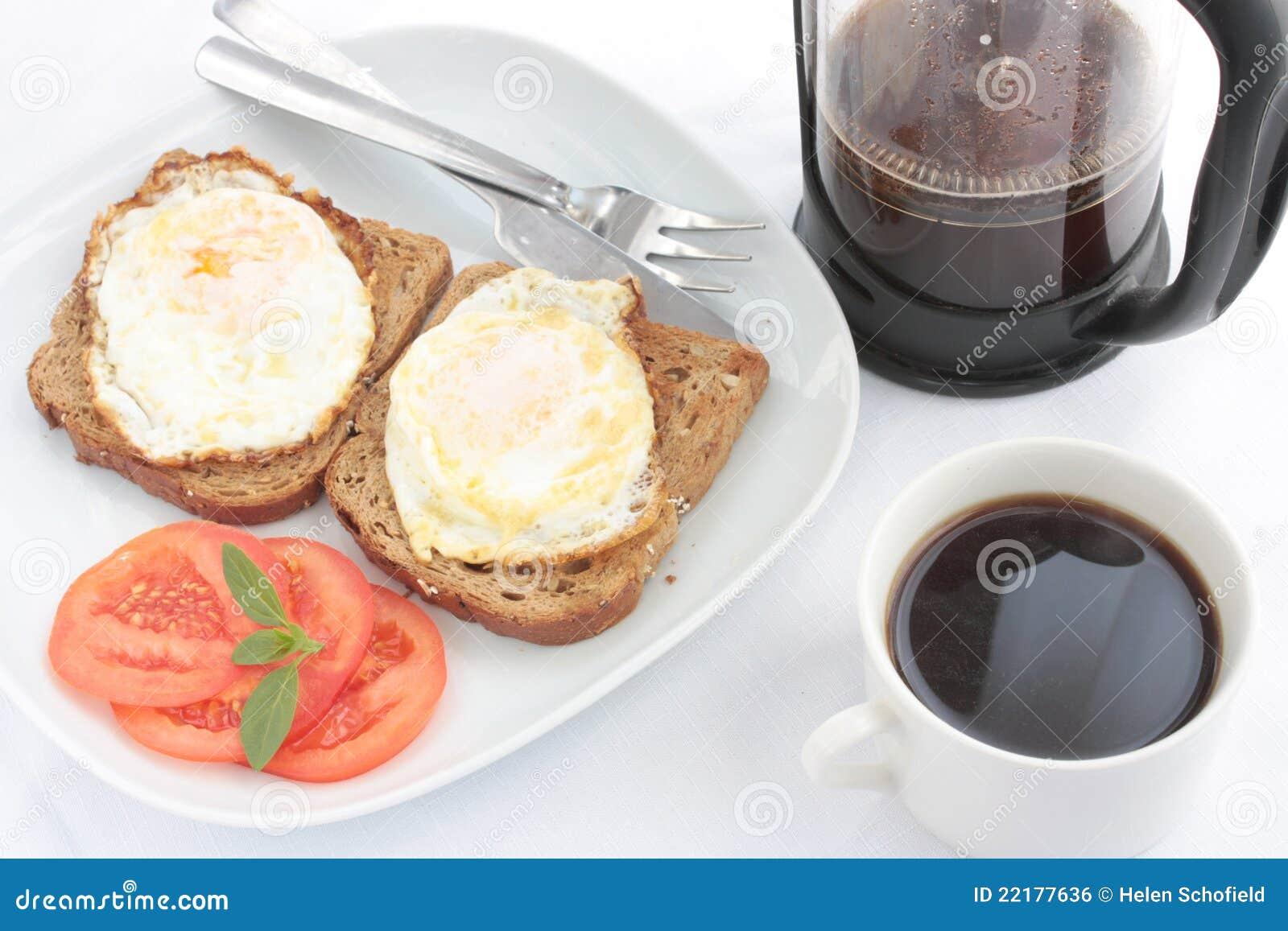 Prima colazione delle uova su pane tostato con caffè