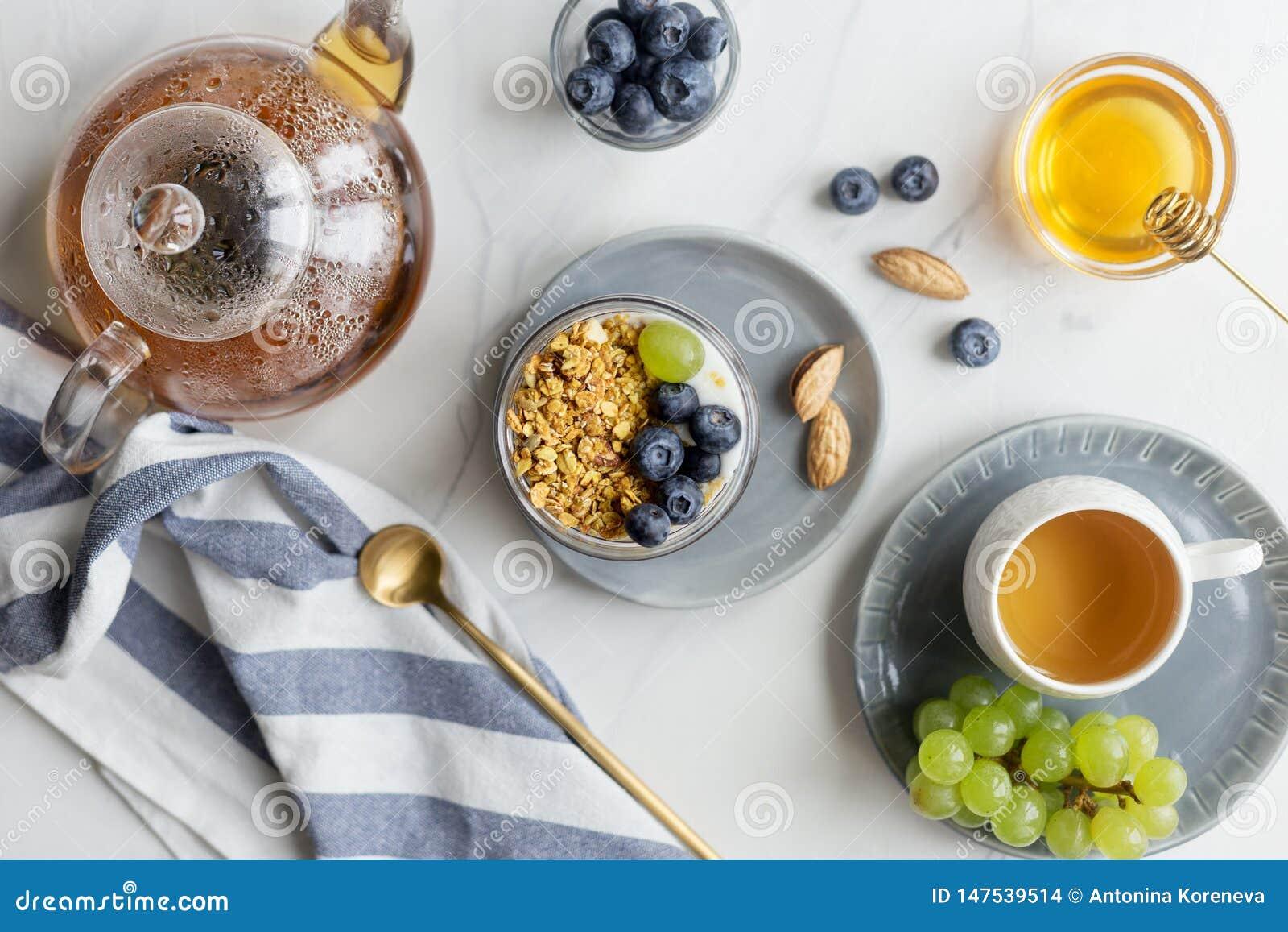 Prima colazione di estate con granola, il mirtillo e l uva con latte