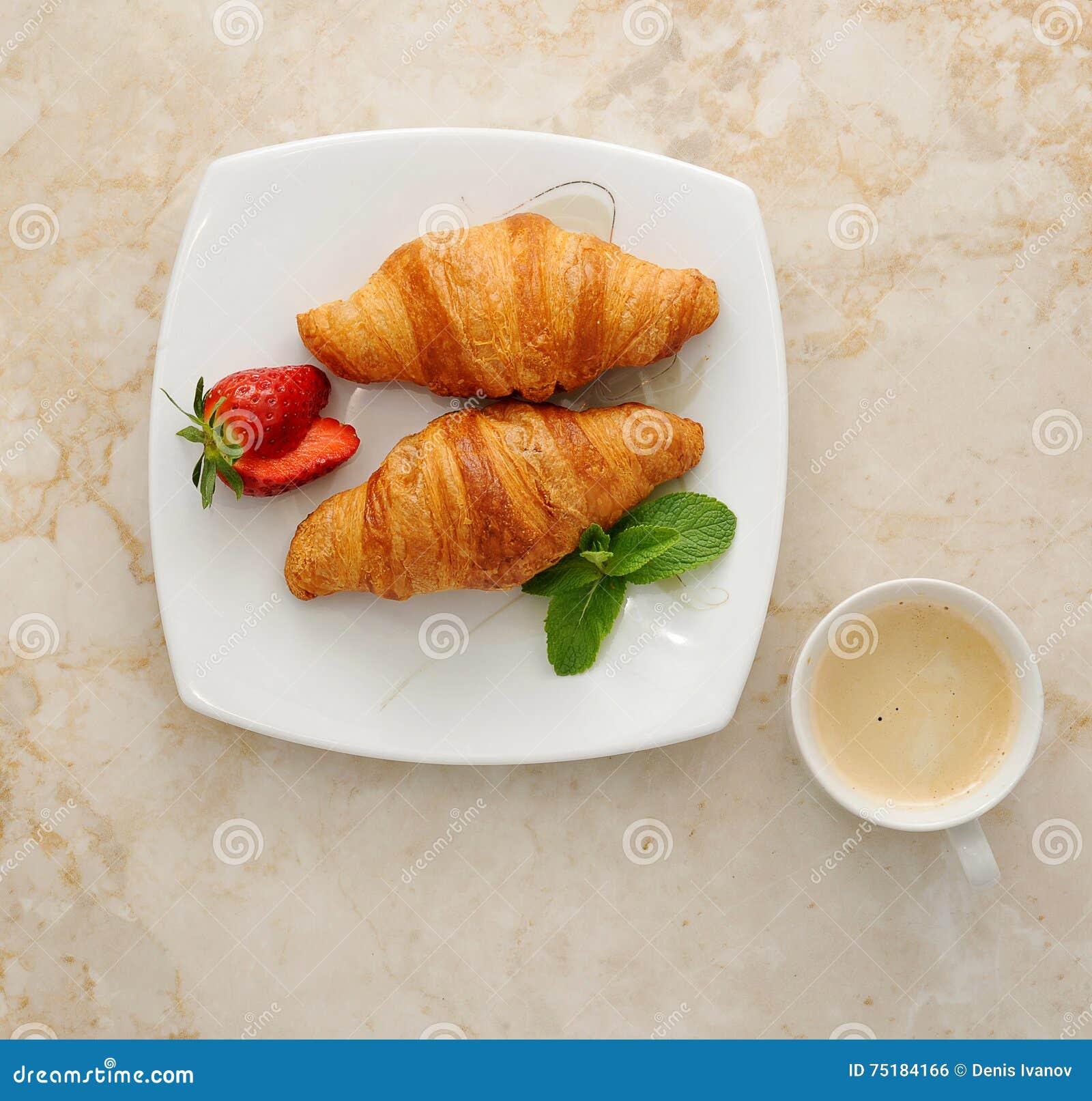 Prima colazione di mattina - croissant con caffè