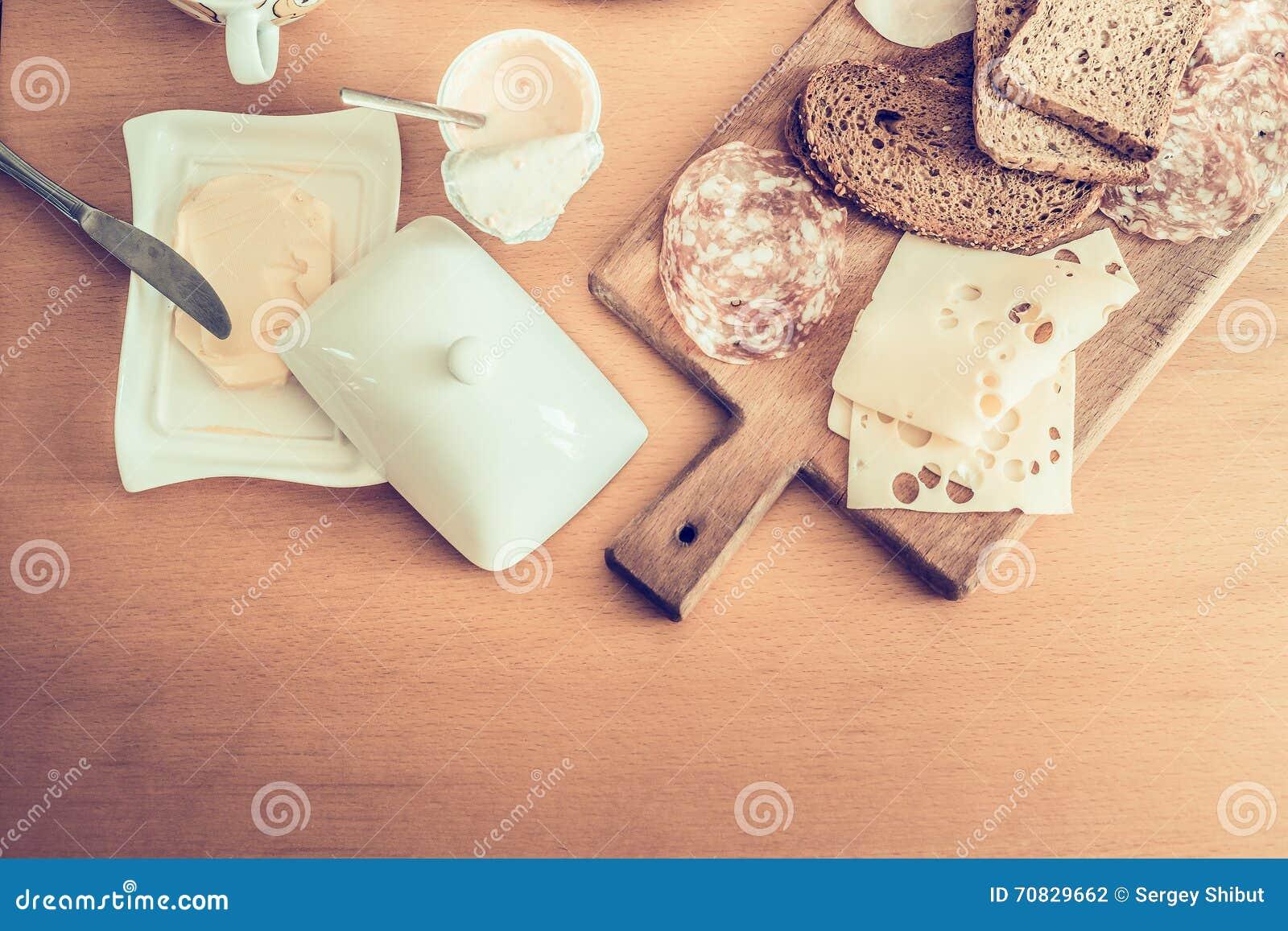 Prima colazione nutriente, ingredienti per produrre i panini con salame, burro e formaggio, yogurt su una vista di legno del pian