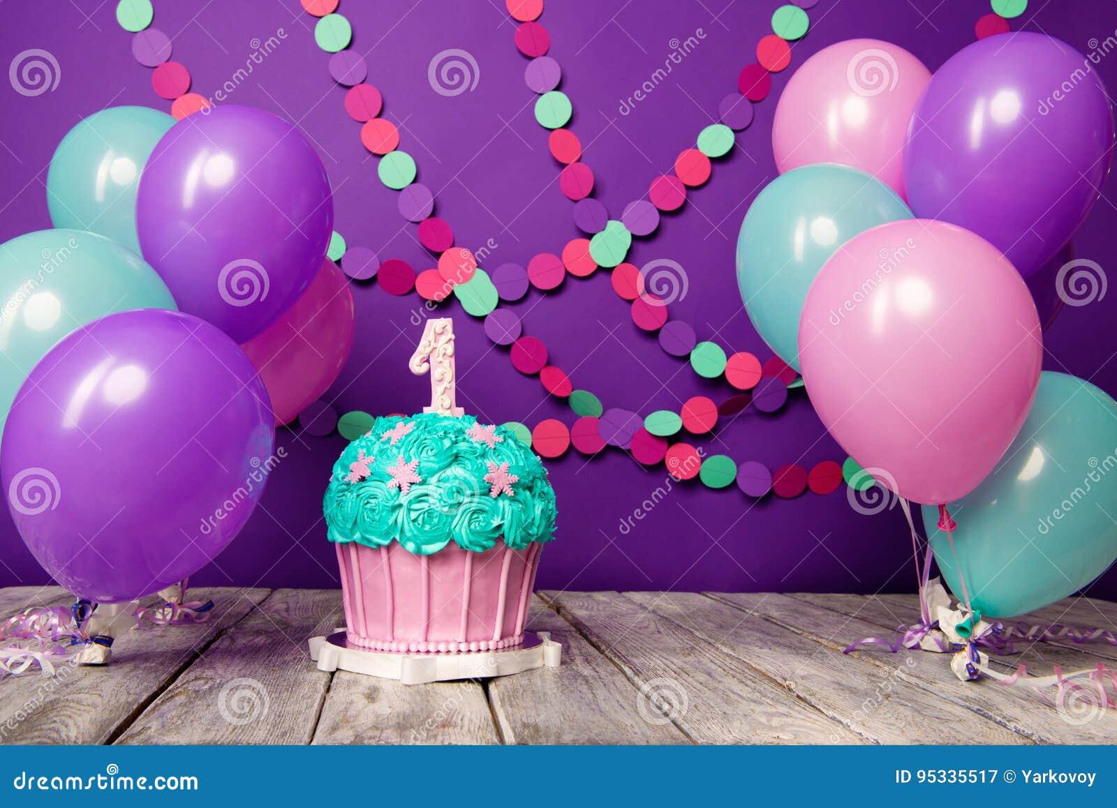 Prima torta di compleanno con un unità su un fondo porpora con le palle e la ghirlanda di carta