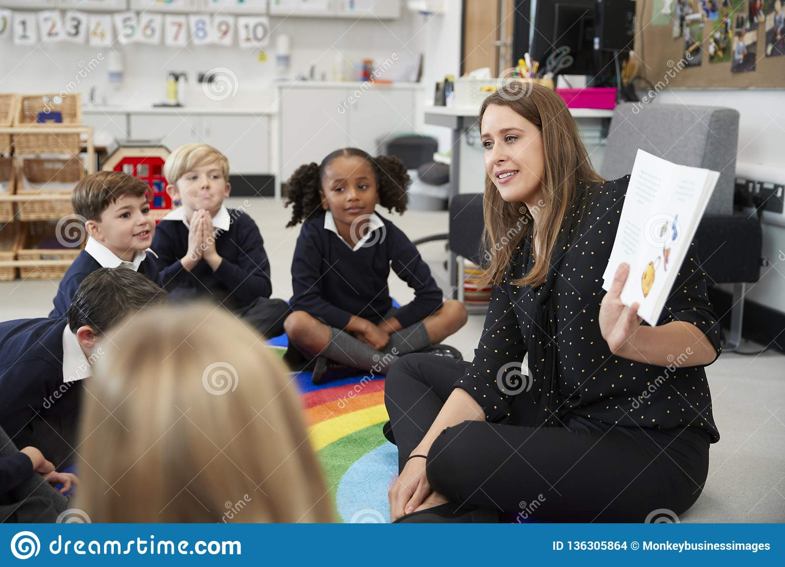 Primary school children sitting on the floor in the classroom with their teacher holding up a book to show them, selective focus