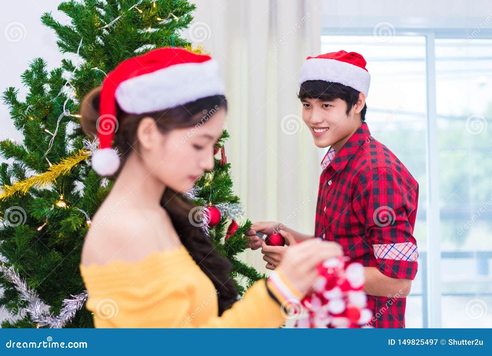 Primeira impressão do homem à mulher que se prepara a decorar a árvore de Natal no festival do ano novo Conceito do Xmas e do eve