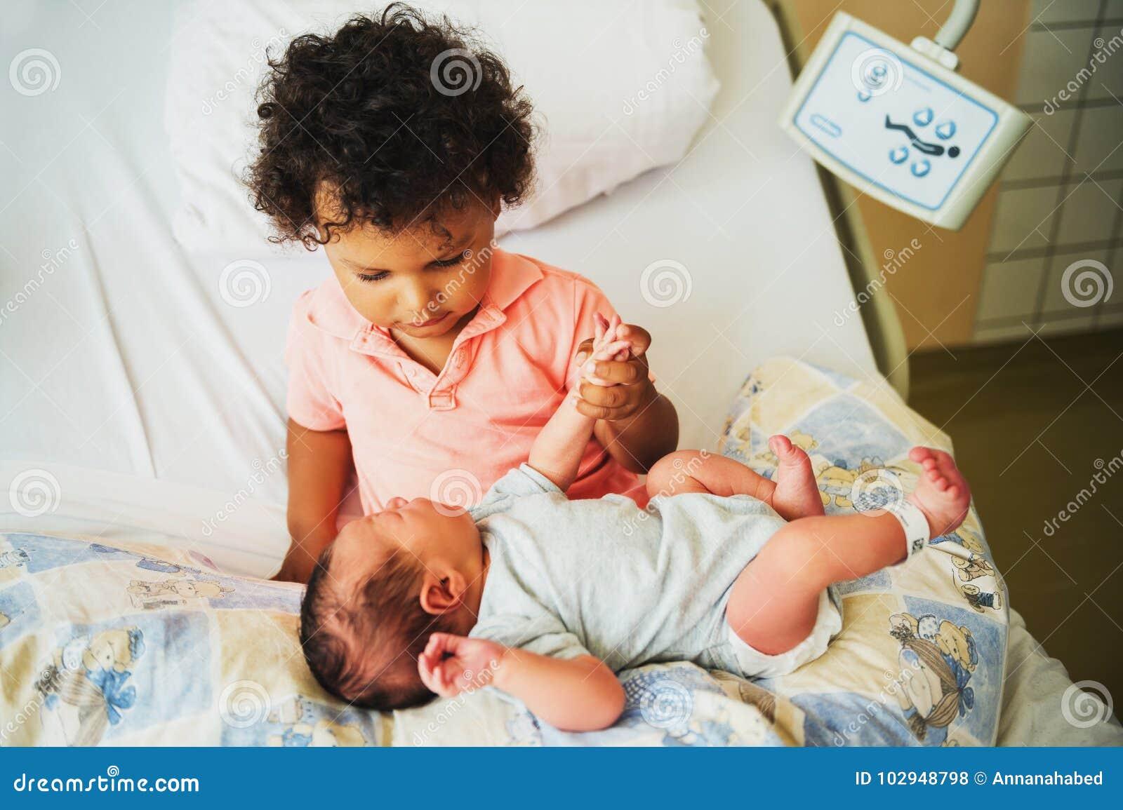 Primeira reunião do menino africano adorável da criança e de seu irmão recém-nascido