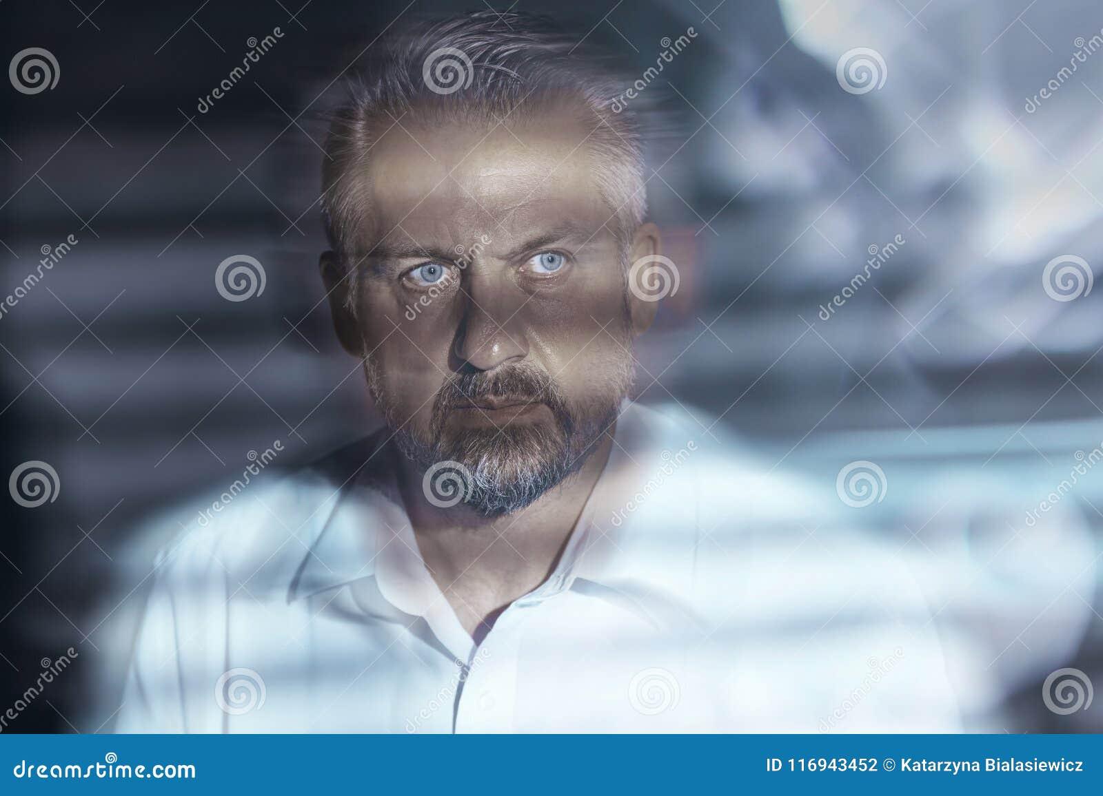 Primer borroso de una cara de mediana edad preocupada del ` s del hombre con los ojos
