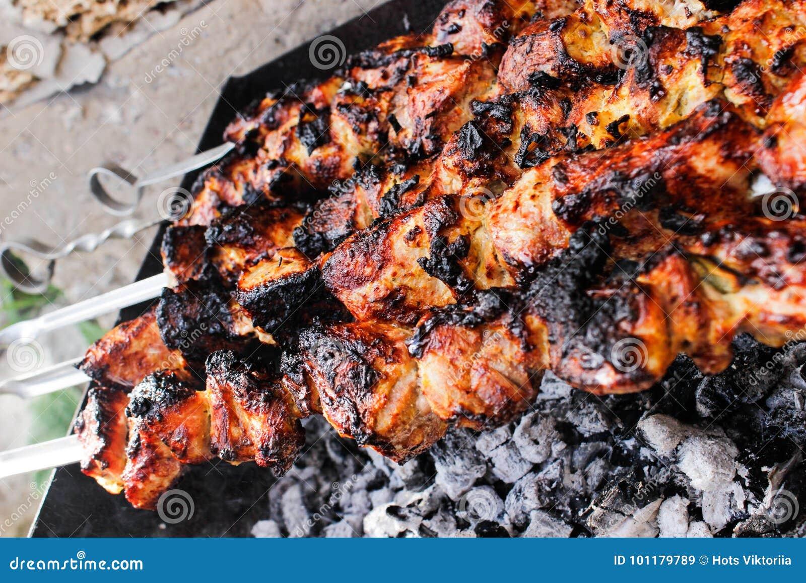 Primer de algunos pinchos de la carne que son asados a la parrilla en una barbacoa