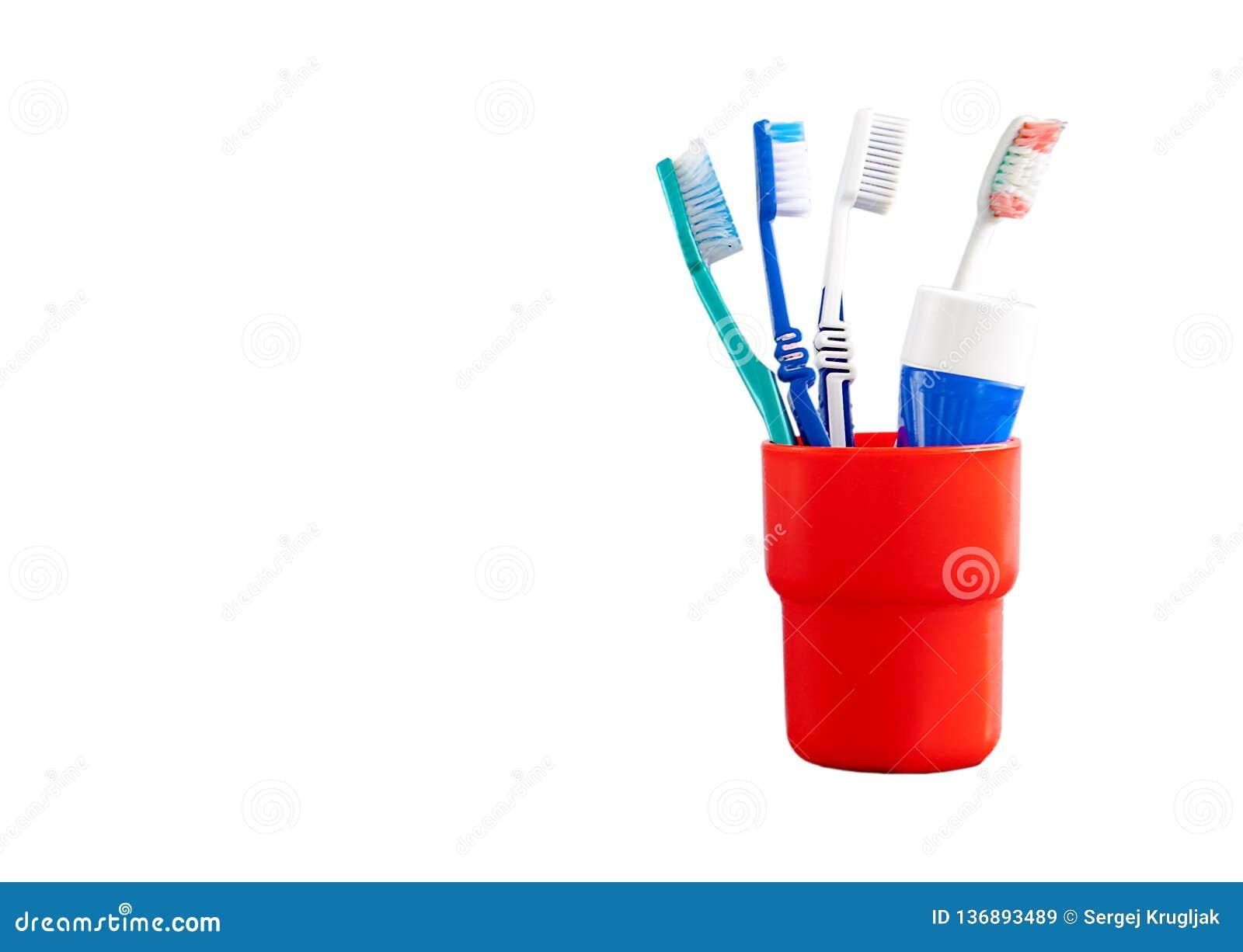 Primer de cepillos de dientes plásticos rojos y azules en una taza roja en un concepto dental del fondo blanco