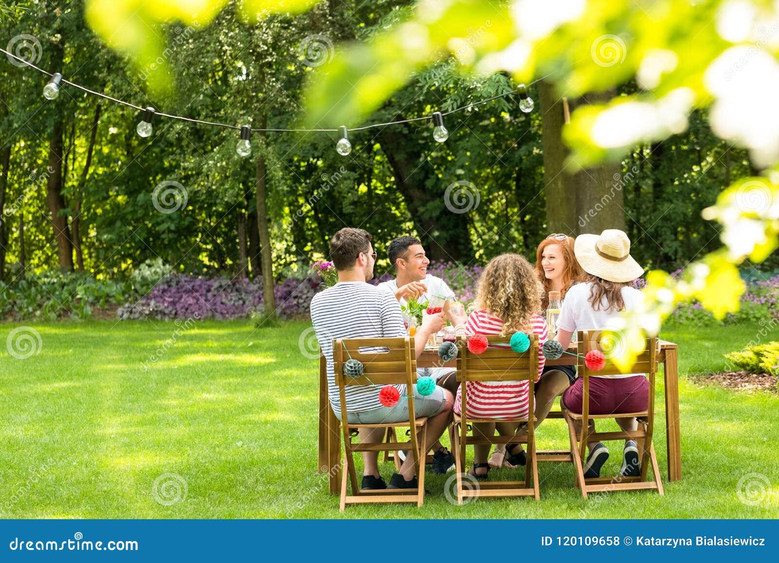 Primer de hojas borrosas en el jardín con un grupo de amigos