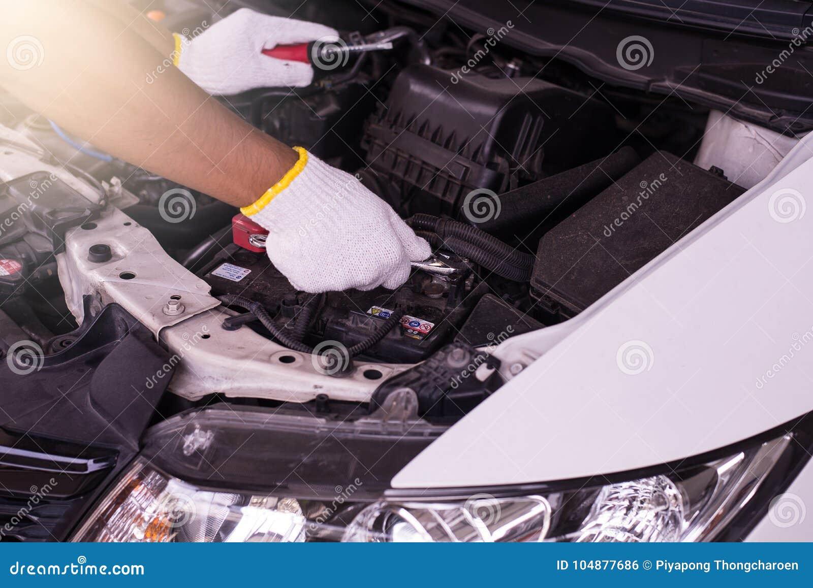Primer de la batería de coche de la fijación del ingeniero del mecánico de la mano en el garaje